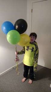 Birthday boy with his balloons.